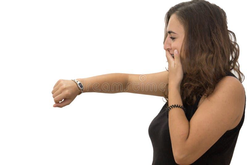 Betontes Mädchen lokalisiert auf dem weißen Hintergrund, der ihre Uhr schaut lizenzfreie stockfotografie