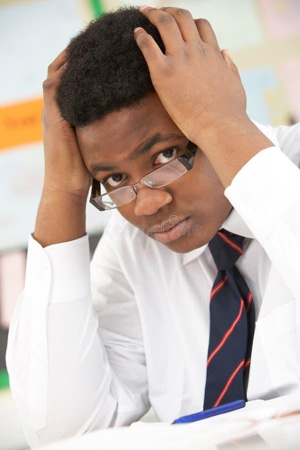 Betontes männliches Jugendkursteilnehmer-Studieren stockfoto