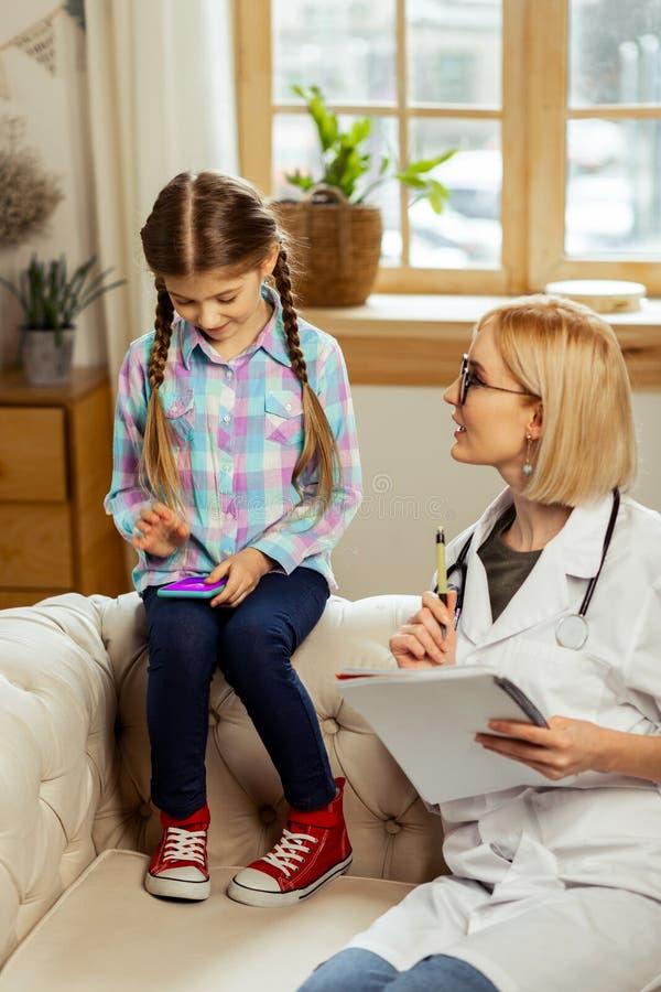 Betoverend pediater het spreken aan een meisje door telefoonspelen dat wordt afgeleid royalty-vrije stock foto's