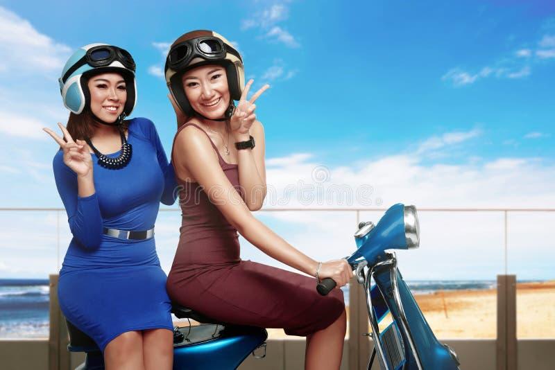Betoverende gelukkige Aziatische vrouw twee die een uitstekende autoped berijden royalty-vrije stock foto's