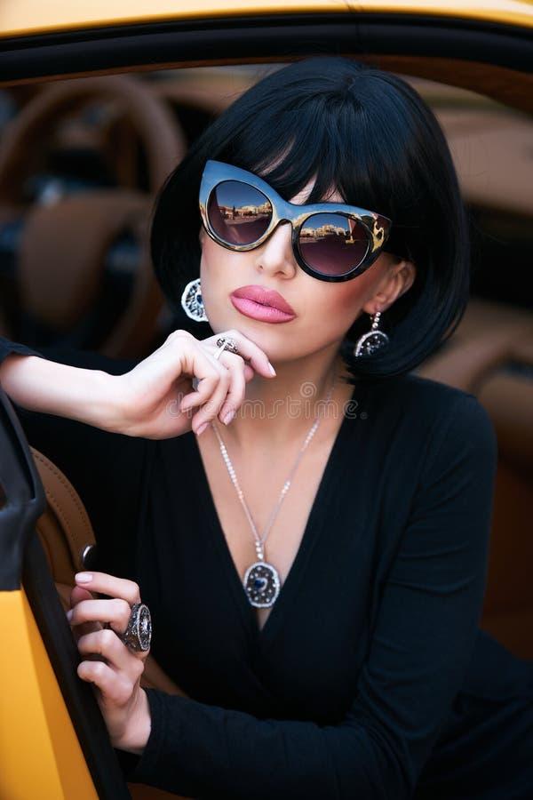 Betoverende Glamour babe zitting in gele supercar stock foto's