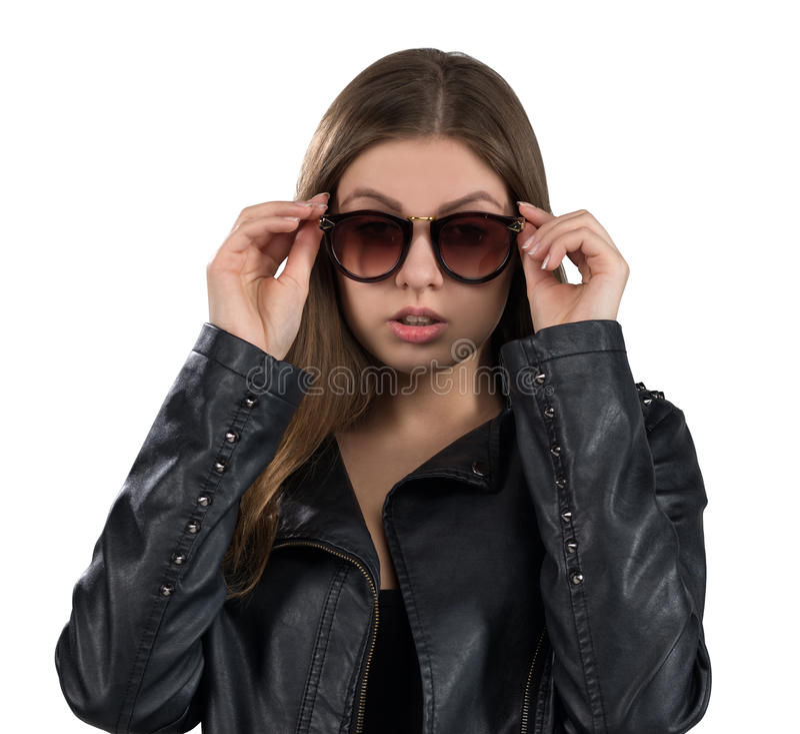 Betoverende hete jonge vrouw in een leerjasje en een bruine die zonnebril, op witte achtergrond wordt geïsoleerd Straat, rotsmani stock foto