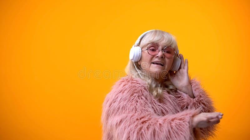Betoverende oude vrouw in hoofdtelefoons het luisteren muziek, die DJ, hobby beweert te zijn stock afbeelding