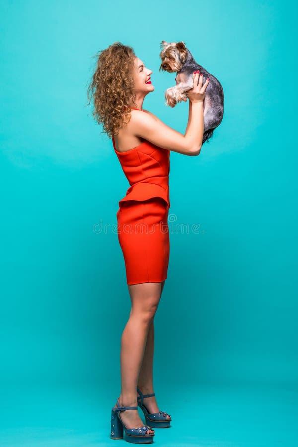 In betoverende stijl Volledige lengte van aantrekkelijke jonge vrouw in mooie rode de terriër van Yorkshire dragen en kleding die stock foto