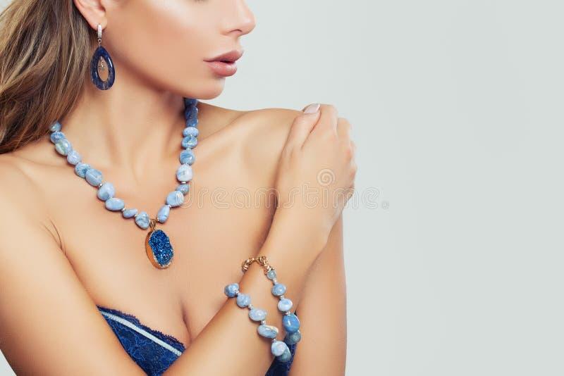 Betoverende vrouw die blauwe halsband, armband en oorringen dragen royalty-vrije stock afbeelding