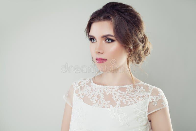 Betoverende vrouw met perfecte make-up en bruids haar op witte achtergrond, vrouwelijke gezichtsclose-up royalty-vrije stock foto