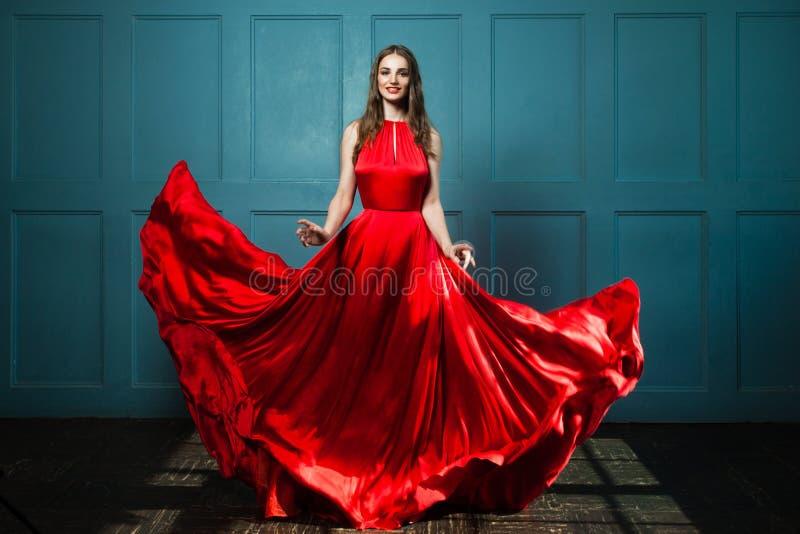 Betoverende Vrouw in Modieuze Rode Kleding stock afbeelding