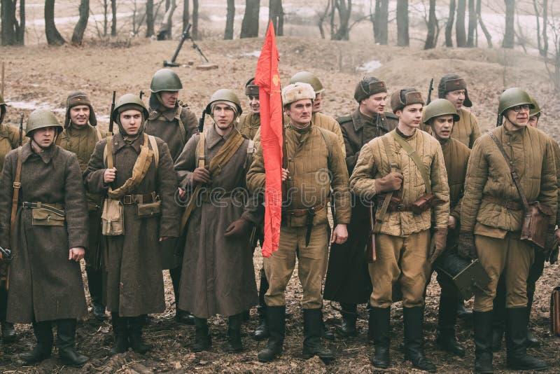 Beträffande-enactors klätt som ryska sovjetiska infanterisoldater av världskrig II som står i rad arkivfoto