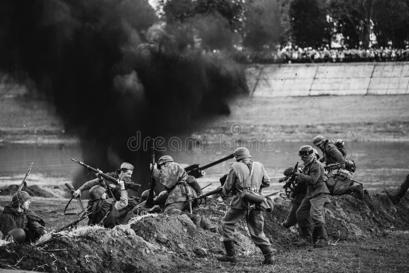 Beträffande-enactors klätt som soldater för tyskWehrmacht infanteri och Ru royaltyfri foto