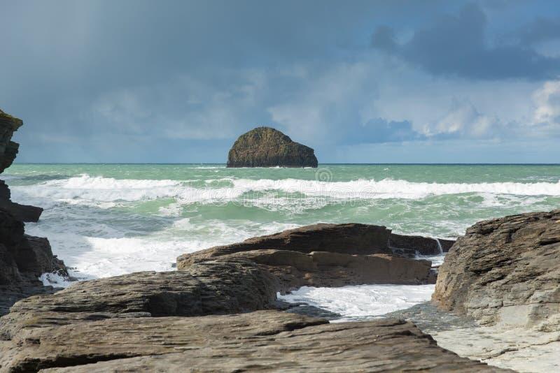 Betrügen Sie Felsen mit dem weißen Wellenbrechen angesehen vom BRITISCHEN Küstendorf Strand Trebarwith-Strang-Cornwalls England stockfotos