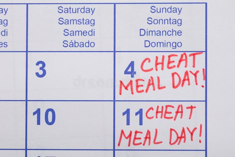 Betrüger-Mahlzeit-Tagestext geschrieben auf Kalender lizenzfreies stockbild