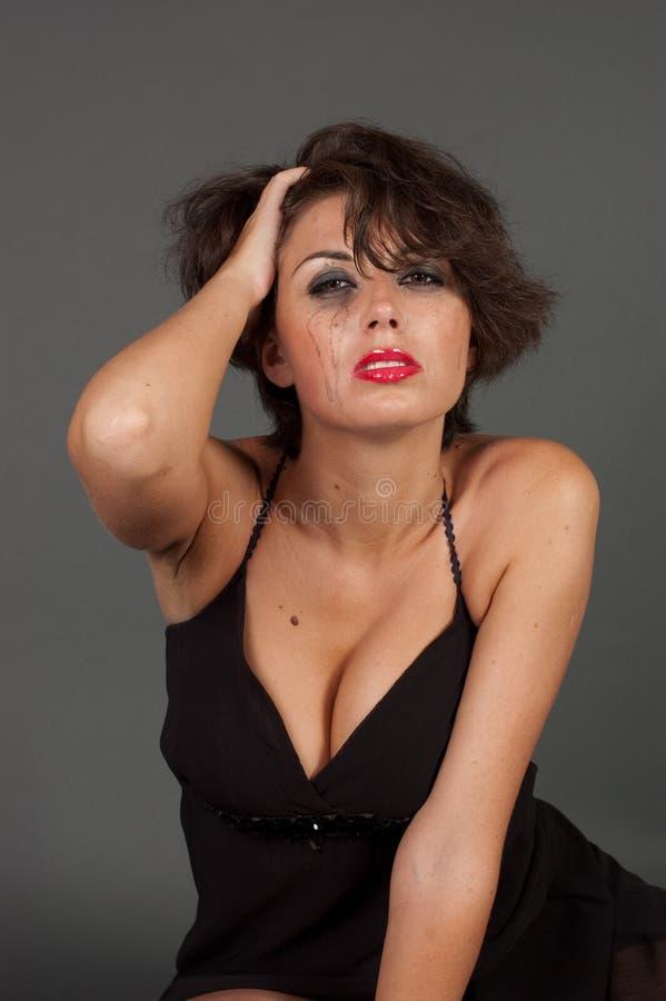 Betraande vrouw in zwarte kleding stock fotografie