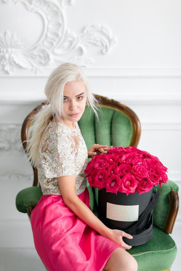 Betrachten der Kamera Junges hübsches Mädchen mit nettem Gesicht und dem langen blonden Haar Frau sitzt und Flugschreiber mit Ros stockbilder
