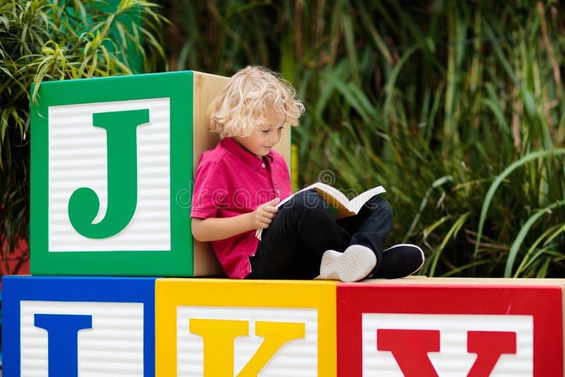 Betrachten der Kamera Kind, das Buchstaben lernt stockfotos