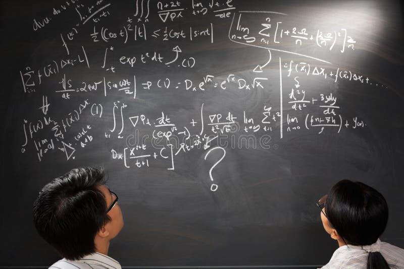 Betrachten der schwierigen komplizierten Gleichung stockfotos