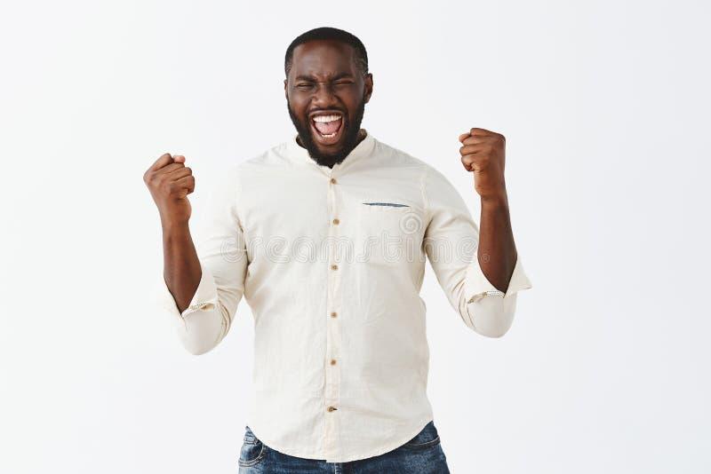 Betrachten Sie meine Energie Porträt des erwachsenen bärtigen Mannes des hübschen Afroamerikaners, der angehobene Fäuste während  stockbilder