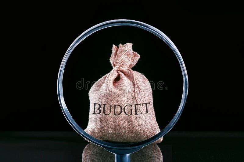 Betrachtet das Budget durch einen Lupenabschluß oben Wirtschaftliche Vermutung stockbild