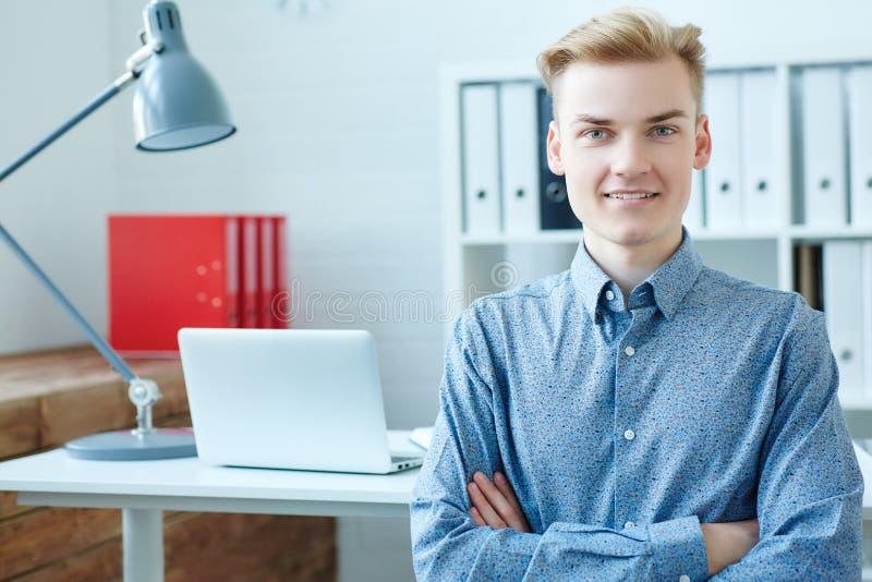 Betrachtet lächelnder kaukasischer Geschäftsmann der Junge die Kamera und sitzt vor seinem Arbeitsplatz mit den gekreuzten Armen lizenzfreie stockfotografie