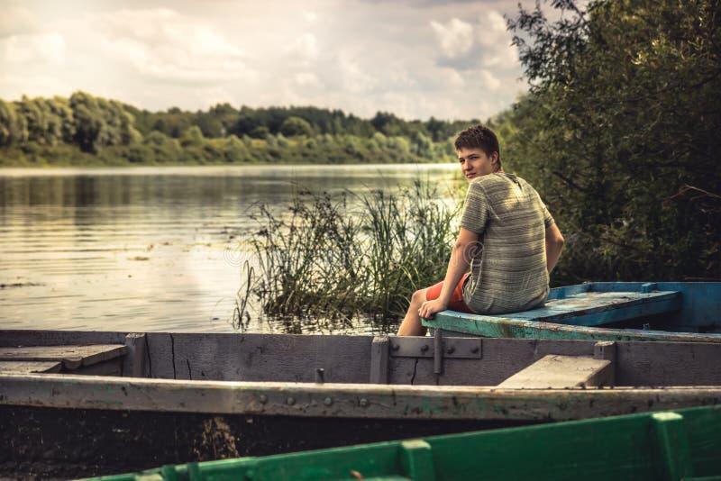 Betrachtungs-Landschaftslandschaft des Jugendlichjungen einsame auf Flussbank während der LandschaftsSommerferien lizenzfreie stockfotografie