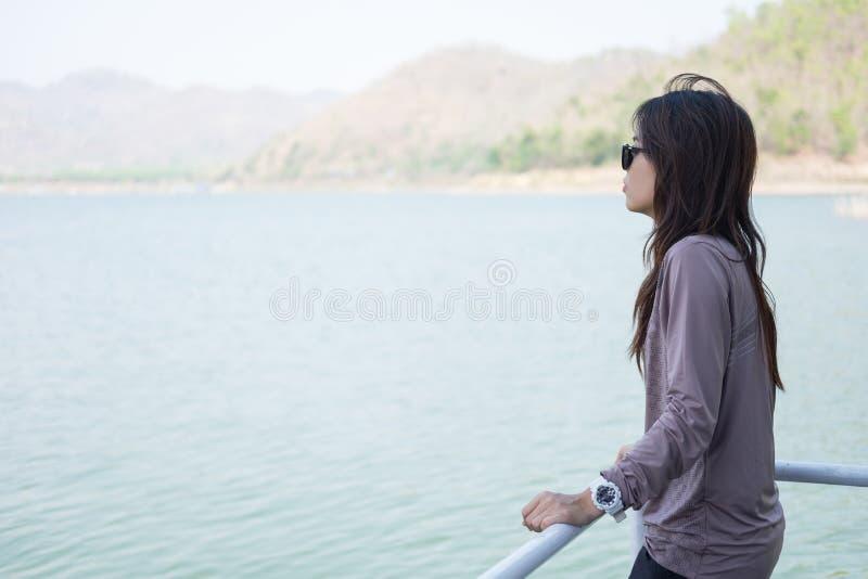 Betrachtungslandschaft des einzigen Momentes der jungen Frau stehende auf Boot frontseite stockfoto