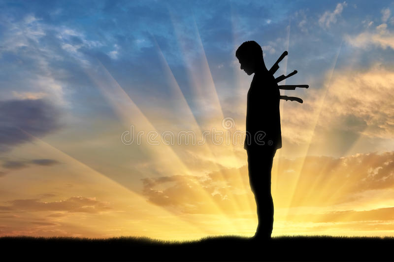 Betrayal and treachery concept. Silhouette of a sad man with a knives in the back on a sunset background royalty free stock images