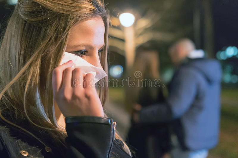 Betrayal. Upset crying girl discovering her boyfriend with another woman royalty free stock images