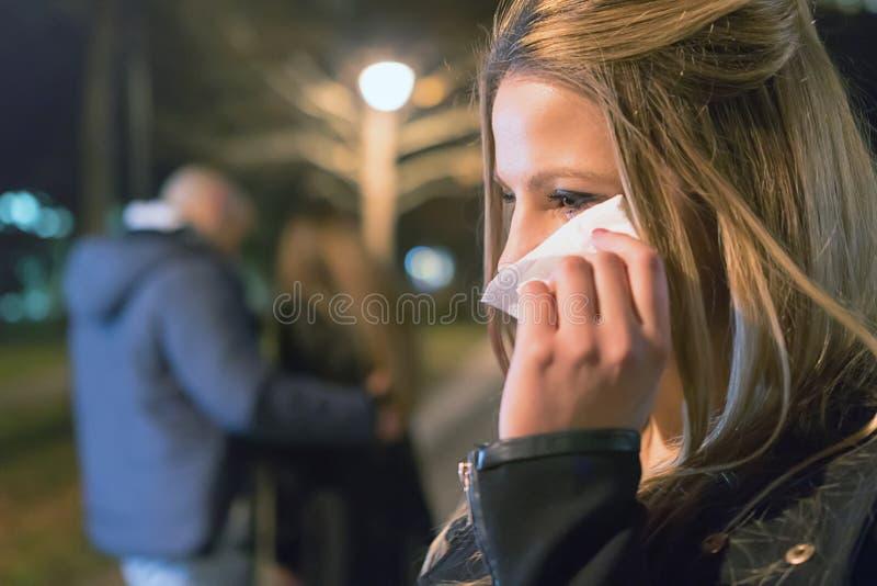 betrayer Расстроенная плача девушка открывая ее парня с другой женщиной стоковая фотография rf