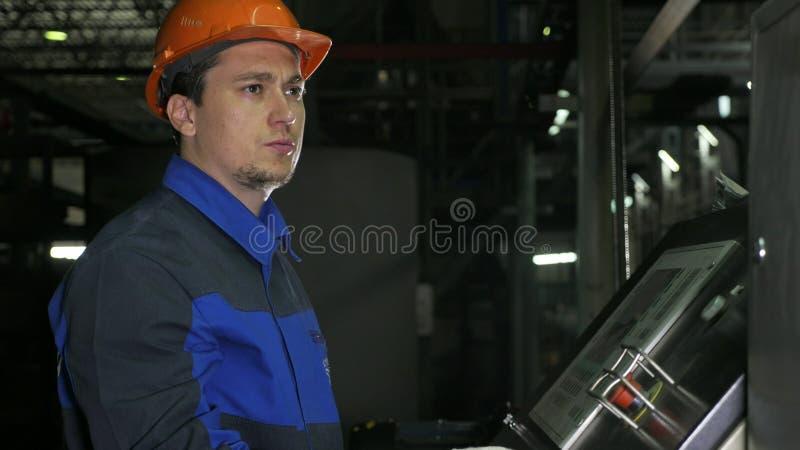 Betreiber überwacht Bedienfeld der Fertigungsstraße Fertigung der Plastikwasserleitungsfabrik Prozess der Herstellung stockfotografie