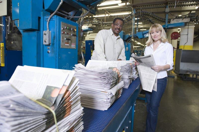 Betreiber, die in der Zeitungs-Fabrik arbeiten stockfotografie
