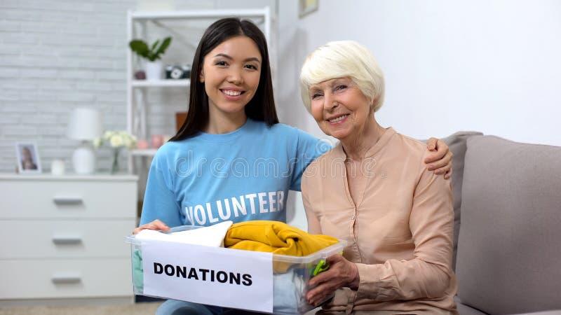 Betreuende Aktivisten, die Frauen im Ruhestand mit Spendenbox, Unterstützung und Betreuung umarmen lizenzfreies stockfoto