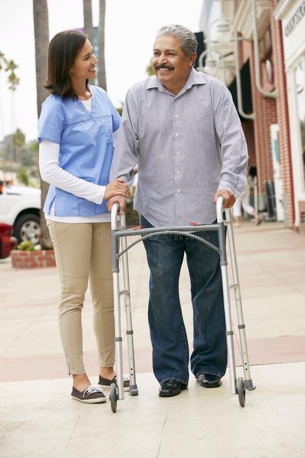 Betreuer, der älterem Mann hilft, gehenden Rahmen zu benutzen lizenzfreies stockfoto