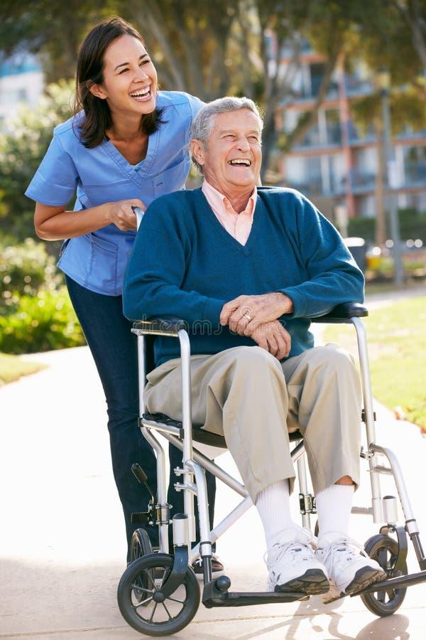 Betreuer, der älteren Mann im Rollstuhl drückt stockfoto