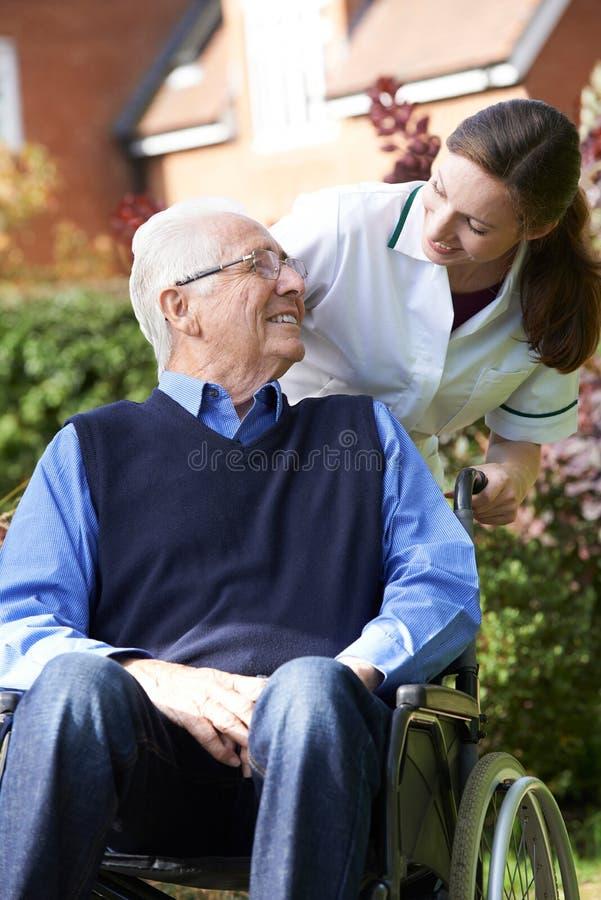 Betreuer, der älteren Mann im Rollstuhl drückt stockbild