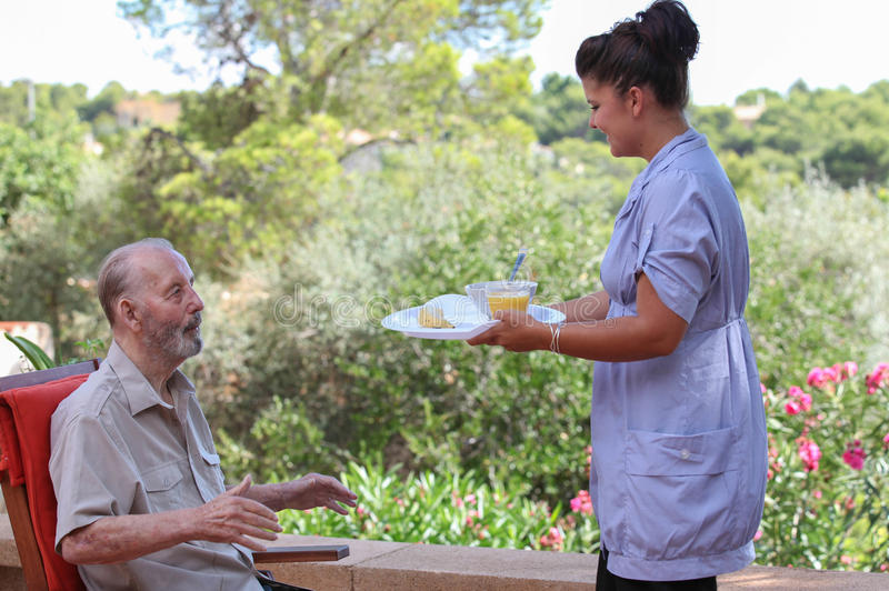 Betreuer, der älteres Lebensmittel im Wohnheim gibt lizenzfreie stockfotos