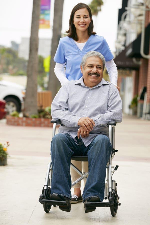 Betreuer, der arbeitsunfähigen älteren Mann im Rollstuhl drückt lizenzfreie stockbilder