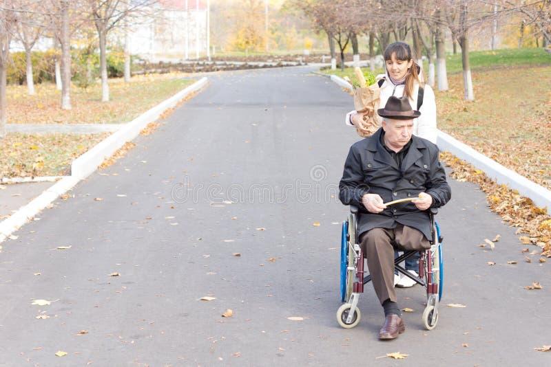 Betreuer, der einem behinderten Mann in einem Rollstuhl hilft stockbilder