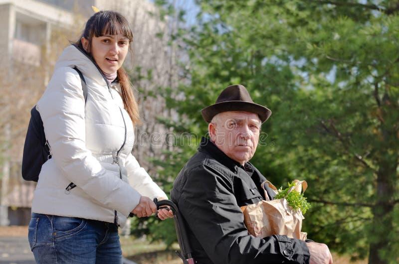 Betreuer, der einem Mann in einem Rollstuhl hilft stockfotos