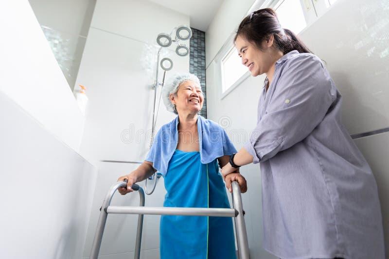 Betreuung der asiatischen Tochter- oder Frauenbetreuung, Hilfe, Unterstützung der älteren Frau, die im Badezimmer Dusche nehmen,  lizenzfreies stockbild