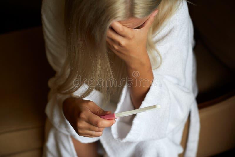 Betrokken Vrouw in Badkamers die de Test van de Huiszwangerschap gebruiken royalty-vrije stock fotografie