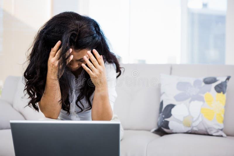 Betrokken vrouwenzitting thuis royalty-vrije stock afbeeldingen