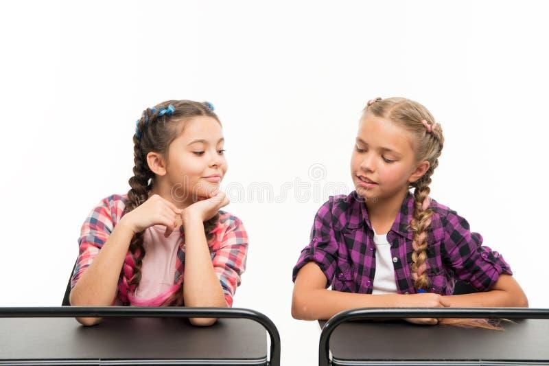 Betrug auf der Prüfung Kleine Schulkinder, welche die Prüfung lokalisiert auf Weiß bestehen Kleines Mädchen, das an ihrem Mitschü stockfotografie
