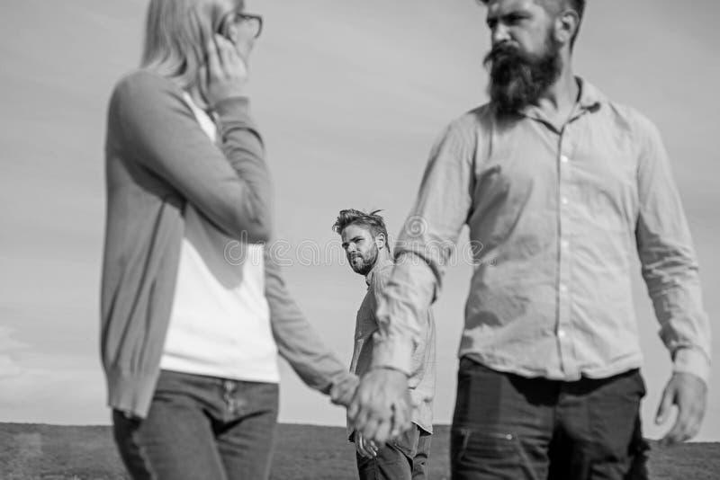Betrugkonzept Mann fand oder ermittelte Freundin, ihn zu betrügen gehend mit einem anderen Mann Des Freundes eifersüchtige Blicke lizenzfreie stockfotos