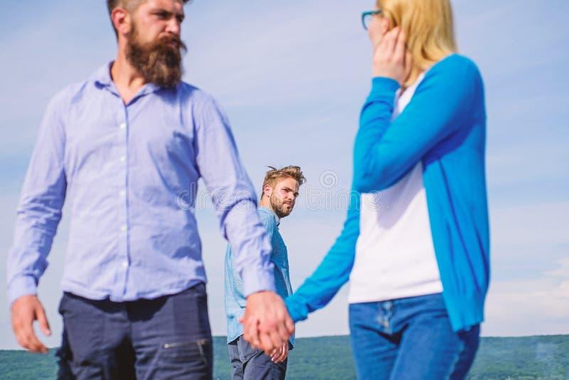 Betrugkonzept Mann fand oder ermittelte Freundin, ihn zu betrügen gehend mit einem anderen Mann Des Freundes eifersüchtige Blicke lizenzfreies stockbild