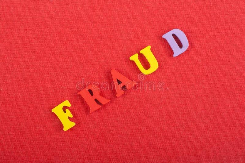 BETRUGS-Wort auf dem roten Hintergrund verfasst von den hölzernen Buchstaben des bunten ABC-Alphabetblockes, Kopienraum für Anzei lizenzfreie stockfotos