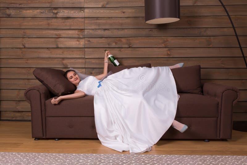 Betrunkene Braut mit Flasche Alkohol entspannen sich auf Couch stockfotografie