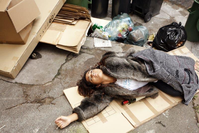 Betrunkene Frau, die im Abfall liegt stockfotos