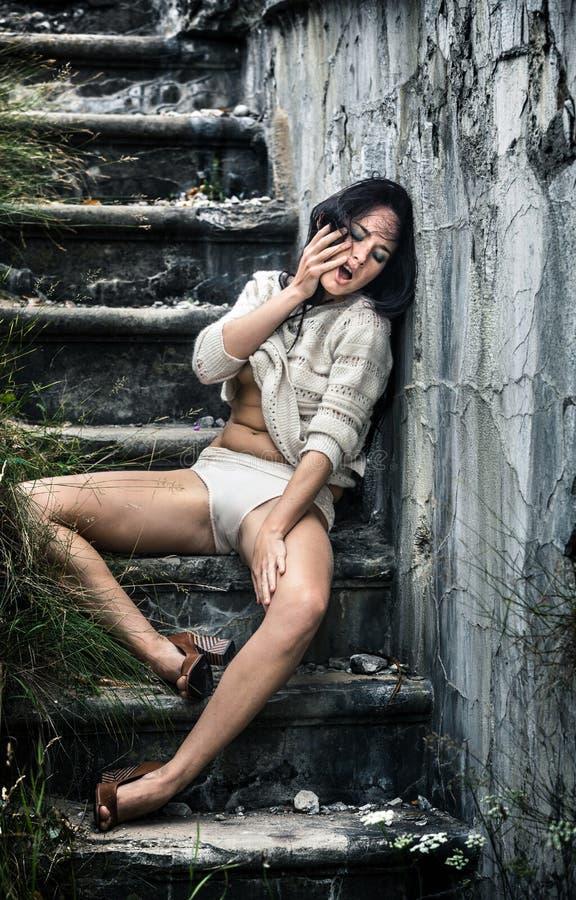 Betrunkene junge Frau auf der Treppe lizenzfreie stockbilder