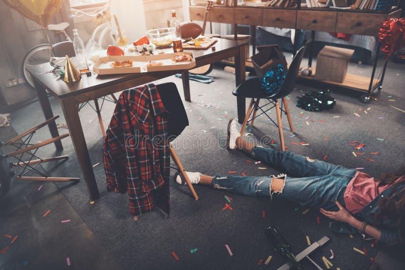 Betrunkene junge Frau, die auf Boden im unordentlichen Raum nach Partei liegt lizenzfreies stockfoto