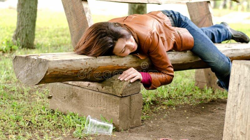 Betrunkene schlafende Frau es weg auf einer Holzbank lizenzfreies stockfoto