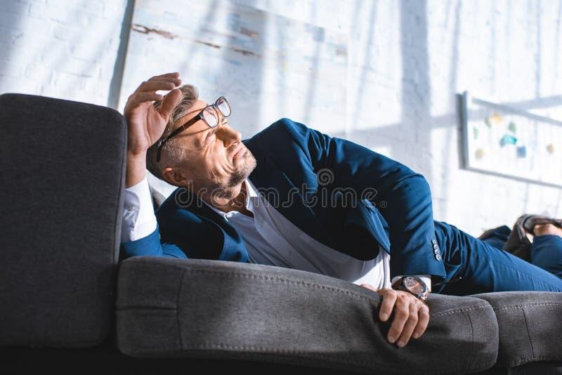 betrunkener Geschäftsmann in den Gläsern, die auf Sofa mit Sonnenschein herein liegen stockbilder